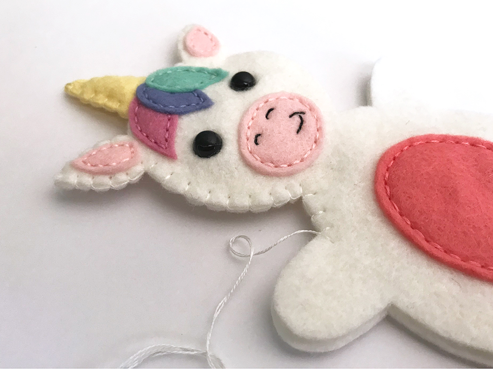 felt unicorn softie free pattern - using blanket stitch to sew the front of the unicorn to the back
